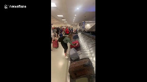 item: 'Tough luck! Woman tries to retrieve suitcase from baggage carousel and ends up spilling all of her belongings'