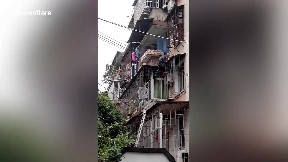 item: 'Brave man rescues elderly woman hanging from first-floor balcony in China'